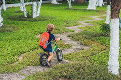 Little boy on a balance bike. Caught in motion, on a driveway. P. Reschool child`s first day on the bike. The joy of movement. Little athlete learns to keep Stock Photography