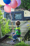 Little boy with balloons. Little boy sitting on a bridge holding balloons Royalty Free Stock Photography