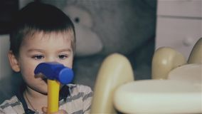 A little boy banging a toy hammer on the table stock video footage