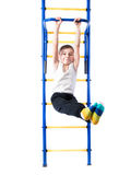 Little boy on the bar whist legs outstretched and smiling Stock Image