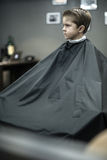 Little boy in barbershop. Dreaming little boy in a black salon cape in the barbershop. He looks to the side. Wide aperture closeup photo. Vertical Stock Image