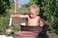 Little boy in a basin, taking a bath in garden stock photography