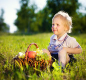 Little boy with a basket of fruit. Sits on a grass Stock Image