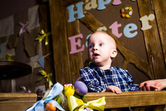 Little boy in a basket of rustic rural Provence hilarious, laugh, smile, joy, beautiful, blue eyes easter, eggs, colorful Royalty Free Stock Images