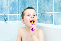 Little boy in the bath tub brushing his teeth Royalty Free Stock Photo