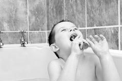 Little boy in the bath tub brushing his teeth Stock Photos