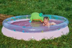 A little boy bathes in round inflatable pool in the open air. The child is wet and hair wet. Boy smiling. He is happy, happy, happy. A child plays in the pool Royalty Free Stock Photo