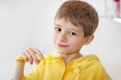 Little boy in bathrobe washing his teeth after evening bath. Beautiful kid preparing to brush their teeth wearing yellow bathrobes. closeup Stock Photography