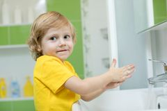 Little boy in a bathroom washes hand with soap stock images