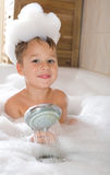 Little boy in a bathtube. Little boy sitting in the tub and plays with the shower stock photo
