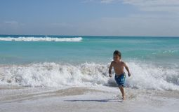 Little boy on the beach. Little boy running on the water playing with the waves on the beach Royalty Free Stock Photo