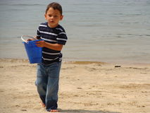 Little boy on the beach. Little boy playing on the lake beach with a blue bucket Royalty Free Stock Photography
