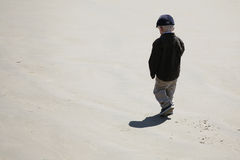 Little Boy on Beach. A little boy walking alone on the beach royalty free stock photo