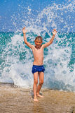 Little boy on the beach with big splashes Royalty Free Stock Images
