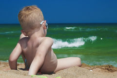 Little boy on the beach. child sitting in sand.Summer.sea.sky Stock Photography
