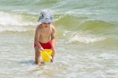 Little boy on the beach collecting water in a bucket toy, playing with sand. Royalty Free Stock Image