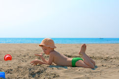 Little boy on the beach. Little boy in panama playing with sand Royalty Free Stock Image