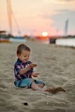 Little boy on the beach, playing with the sand on sunset Royalty Free Stock Photography