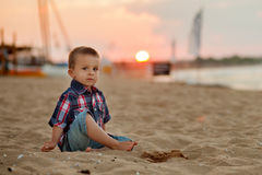 Little boy on the beach, playing with the sand on sunset Royalty Free Stock Images