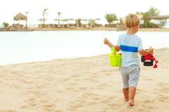 Little boy on a beach with toys. Sea view. Copy space royalty free stock photo