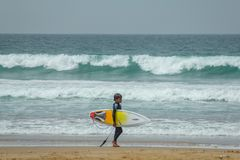 Little boy at the beach with yellow surfboard on the Atlantic Ocean with waves stock photography
