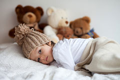 Little boy in bed with teddy bears around Royalty Free Stock Images