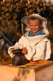 Little boy beekeeper works on an apiary at hive Stock Photography