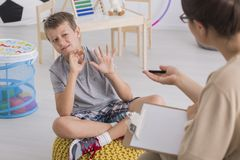 Little boy with behavioral problems. Little stubborn boy with behavioral problems refusing to work with female child therapist Stock Image