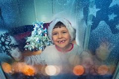 Little boy behind frozen window before Christmas royalty free stock image
