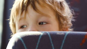 Little boy behind the seat in the bus Stock Photography
