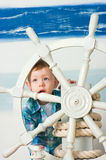 Little boy behind a ship steering wheel Stock Image