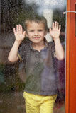 Little boy behind the window in the rain Royalty Free Stock Photos