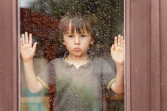 Little boy behind the window in the rain Royalty Free Stock Images