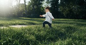 Little boy being adventurous and loving childhood by running through a field exploring. The child runs full of life. 4k stock video