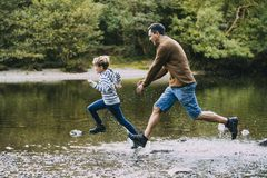 Being Chased in to the Water by Dad. Little boy is being chased in to the lake by his father while they are out hiking Stock Image