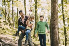 Being Helped on to the Rope Swing. Little boy is being helped on to a rope swing in the woodlands by his father and brother stock photo
