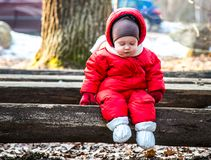 Little boy on a bench. Little boy in outdoors sitting on a bench Royalty Free Stock Photos