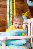Little boy on bench with pillows indoors Stock Photos