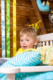 Little boy on bench with pillows indoors Royalty Free Stock Photo