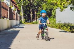 Little boy on a bicycle. Caught in motion, on a driveway motion. Blurred. Preschool child`s first day on the bike. The joy of movement. Little athlete learns to Stock Photos