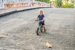 Little boy on a bicycle. Caught in motion, on a driveway motion blurred. Preschool child`s first day on the bike. The. Joy of movement. Little athlete learns to royalty free stock images