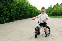 Little boy on a bicycle. Caught in motion, on a driveway. Presch. Ool child`s first day on the bike. The joy of movement. Little athlete learns to keep balance stock photos