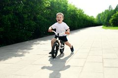 Little boy on a bicycle. Caught in motion, on a driveway. Presch. Ool child`s first day on the bike. The joy of movement. Little athlete learns to keep balance royalty free stock photo