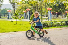 Little boy on a bicycle. Caught in motion, on a driveway. Preschool child`s first day on the bike. The joy of movement. Little at. Hlete learns to keep balance stock image