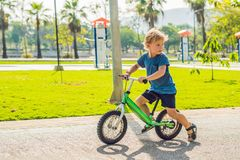 Little boy on a bicycle. Caught in motion, on a driveway. Preschool child`s first day on the bike. The joy of movement. Little athlete learns to keep balance stock photos