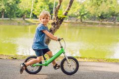 Little boy on a bicycle. Caught in motion, on a driveway. Preschool child`s first day on the bike. The joy of movement. Little athlete learns to keep balance royalty free stock photos