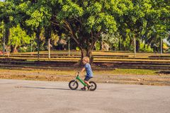 Little boy on a bicycle. Caught in motion, on a driveway. Preschool child`s first day on the bike. The joy of movement. Little athlete learns to keep balance stock images