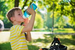 Little boy with bicycle drinks water in park Stock Image