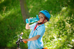 Little boy with bicycle drinks water Royalty Free Stock Photography