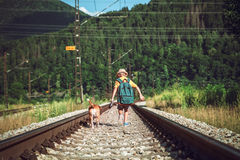 Little boy with big backpack and his beagle dog run on railway Stock Photos